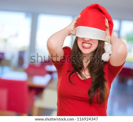 angry woman with a christmas hat covering her eyes, indoor