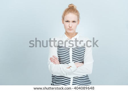 Angry woman with arms folded standing isolated on a white bakground - stock photo