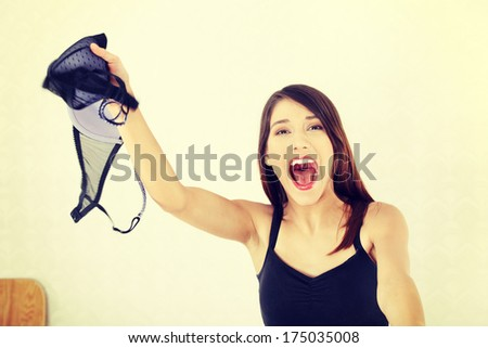 Angry woman with bra in hand. Betrayal concept - stock photo