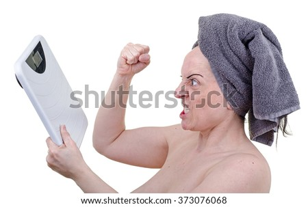 Angry woman with raised fist furious at bathroom weighing scales. White background. - stock photo