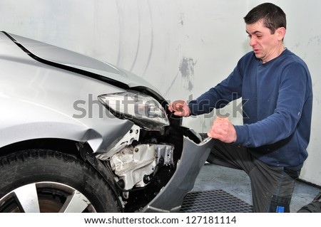 Angry worker repairing a car in a different way. - stock photo
