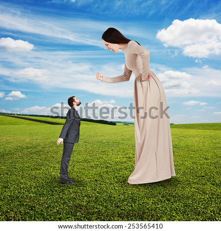 angry yelling woman showing fist and looking down at small kissing man. concept photo at outdoor - stock photo