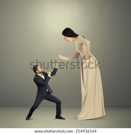 angry yelling woman showing fist to small scared man. photo over dark background - stock photo