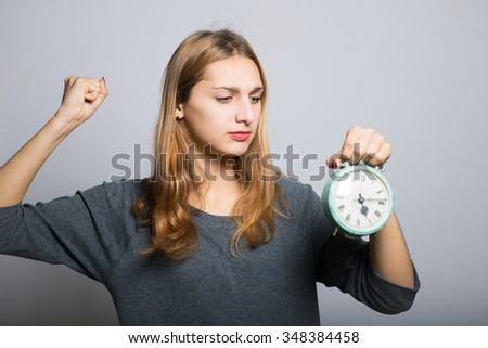 Angry young beauty attacking alarm clock
