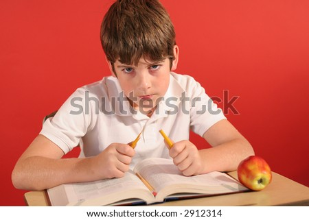 angry young boy breaking pencil at desk - stock photo