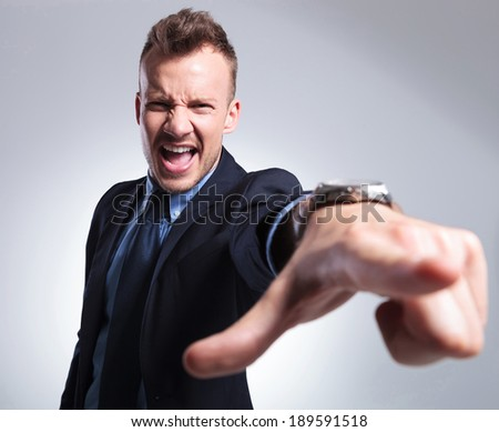 angry young business man shouting and pointing at the camera. gray background
