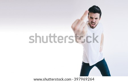 Angry young business man showing  fingers at the camera. - stock photo