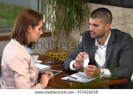 Angry young businessman crumbling some paperwork during the meeting with his colleague in a coffee shop - stock photo