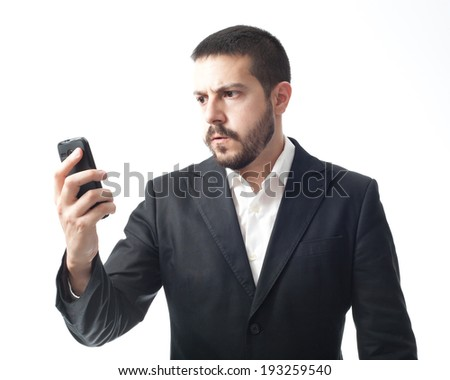 Angry young businessman looking mobile phone.