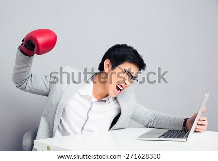 Angry young businessman sitting at the table and reading to hit the laptop over gray background - stock photo