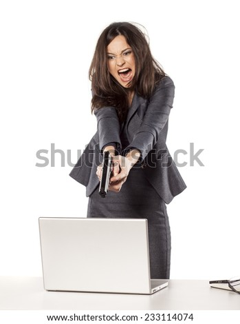 angry young businesswoman wants to shoot at her laptop with a gun - stock photo