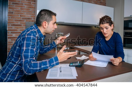 Angry young couple arguing by credit card debts - stock photo