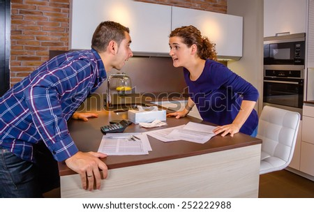 Angry young couple shouting in a hard quarrel by their many debts at home. Financial family problems concept. - stock photo