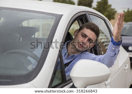 Angry young driver moving his hand at a traffic jam - view from outside