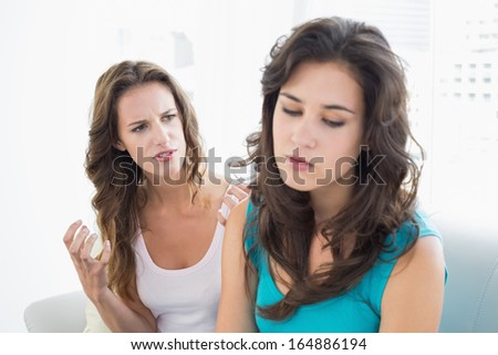 Angry young female friends having an argument in the living room at home - stock photo