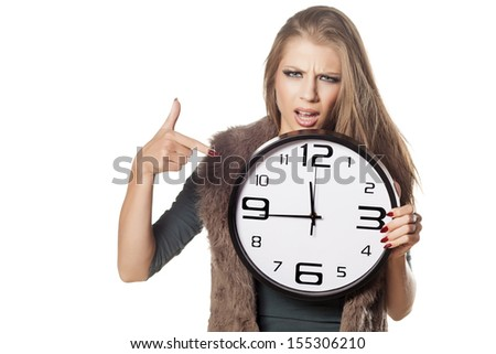 angry young girl holding a clock and pointing a finger at him on white background - stock photo
