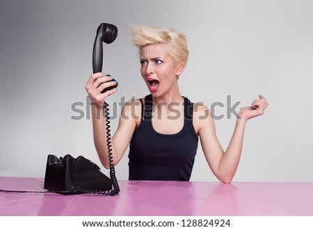 angry young lady shouting and holding handset in her hand - stock photo