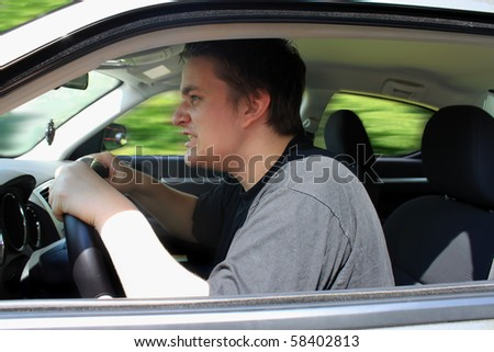 Angry young male driver speeding very fast showing anger as roadrage