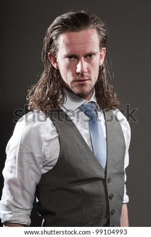 Angry young man brown long hair with expressive face wearing grey suit and blue tie. Isolated on grey background.