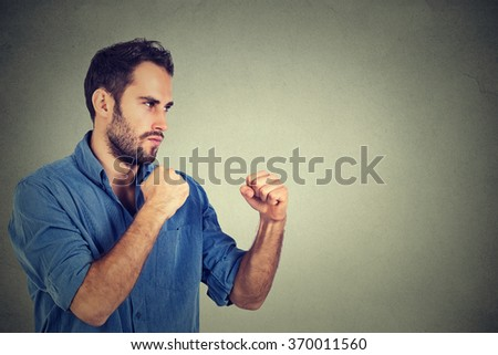 Angry young man clenching his fists - stock photo
