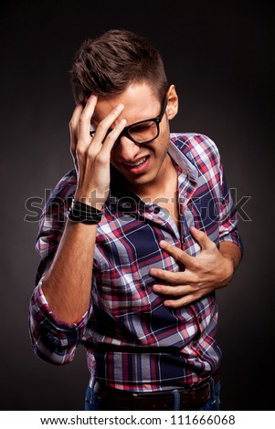 Angry young man doing a frustration gesture over a black background - stock photo