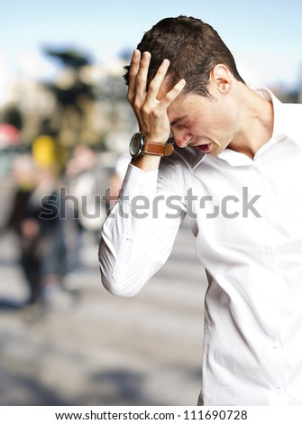 Angry young man doing frustration gesture at crowded place - stock photo