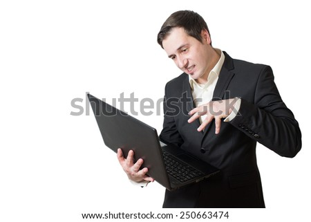 Angry young man in suit holding a laptop isolated over the white background. Studio portrait office worker.  - stock photo
