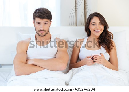 Angry young man lying on the bed with a woman at home - stock photo