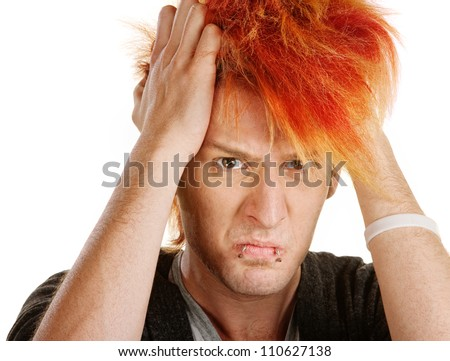 Angry young man pulling his orange hair - stock photo