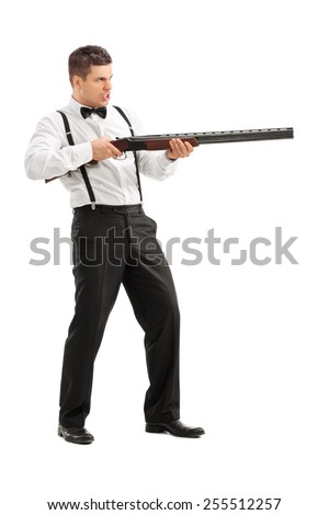 Angry young man shooting at something with a shotgun isolated on white background