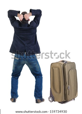 angry young man traveling with suitcas . Rear view. isolated over white. - stock photo