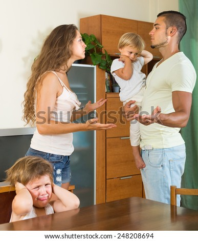 Angry young man with wife and two little daughters having conflict at home - stock photo