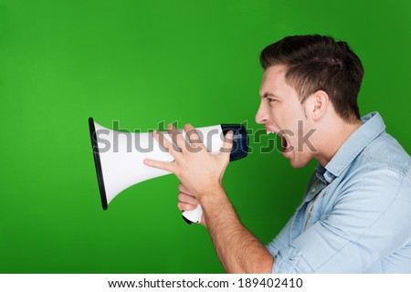 Angry young man yelling into a megaphone or loud-hailer voicing his antagonsim and protest, side view against a green studio background with copyspace - stock photo