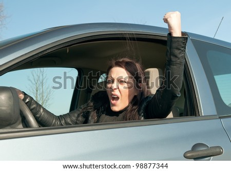 angry young woman in the car shows the fist - stock photo