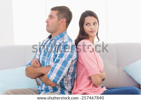 Angry young woman looking at man while sitting on sofa at home - stock photo