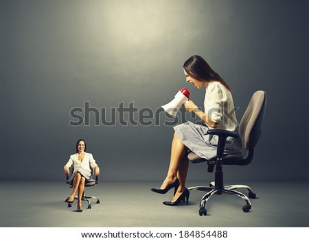 angry young woman screaming at smiley calm woman on the chair over dark background - stock photo