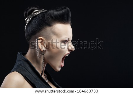 angry young woman screaming isolated on black background with copyspace - stock photo