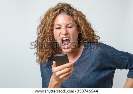 Angry young woman shouting at her mobile with her mouth wide open as she reads a text message on the screen