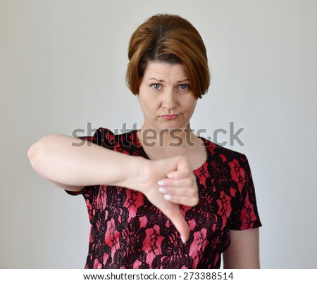 angry young woman showing her thumb down - stock photo
