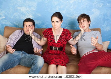 Angry young woman slaps two men on sofa - stock photo