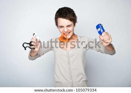 Angry young woman with antistress toys - stock photo
