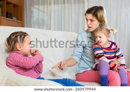 Angry young woman with child on arms shaming daughter - stock photo