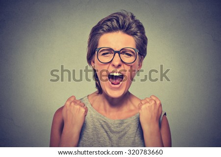 Angry young woman with glasses screaming fists up in air  - stock photo