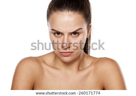 angry young woman with no makeup on a white background - stock photo
