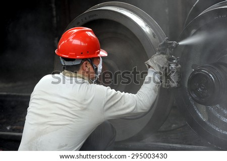 Anhui, Huaibei, China, May 18, 2015, a railway freight car repair work in spray paint.