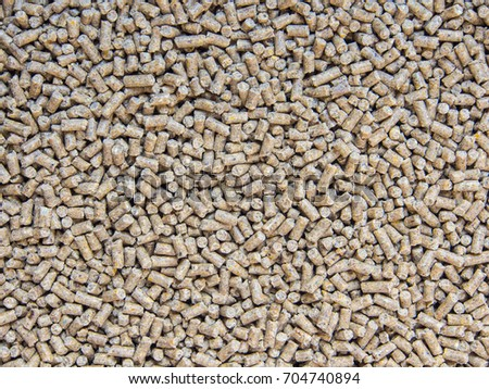 Animal feed pellets as background.