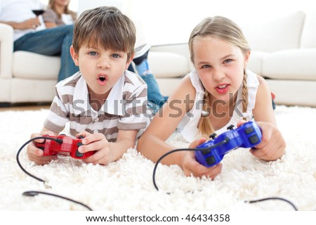 Animated children playing video games lying on the floor - stock photo
