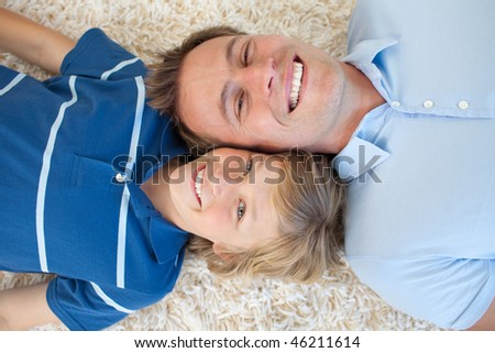 Animated father and his son lying on the floor with heads together - stock photo