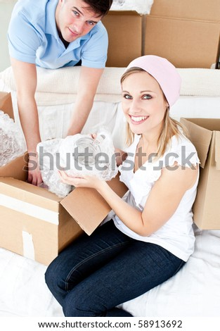 Animated young couple packing a box at home