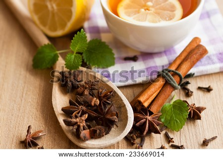 Anise, cinnamon, mint leaf and tea with lemon on wooden background - stock photo
